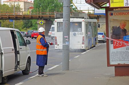 Russia, Moscow - August 15, 2015: Worker washing the light post with water hose at the bus stop in Moscow Editorial
