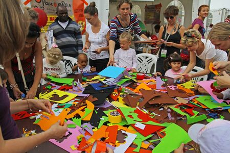 Moscow, Russia - August 18, 2012: Children make applications of colored paper at a childrens master class in park Gorkogo in Moscow