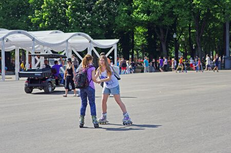 Moscow, Russia - May 19, 2013: Young women learn to roller skate in park Gorkogo in Moscow