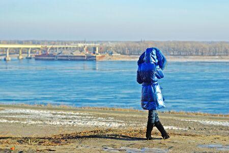 Rear view of woman in a blue coat standing on the bank of the river