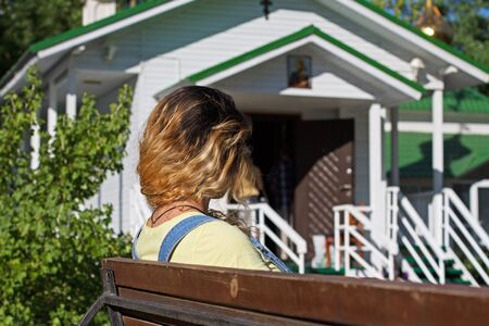 Rear view of woman sitting on a bench in front of a wooden church Stock Photo