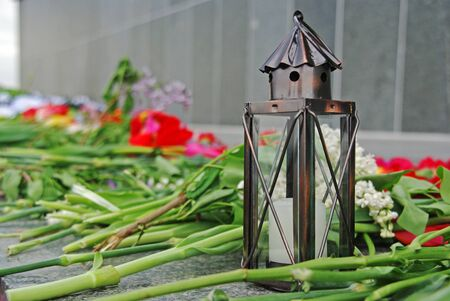 Metal lamp with candle and flowers on the day of remembrance and sorrow Stock Photo