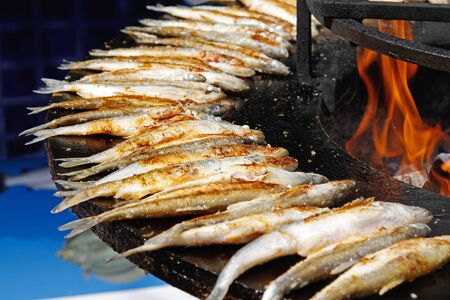 Fried smelts on large barbecue fire bowl
