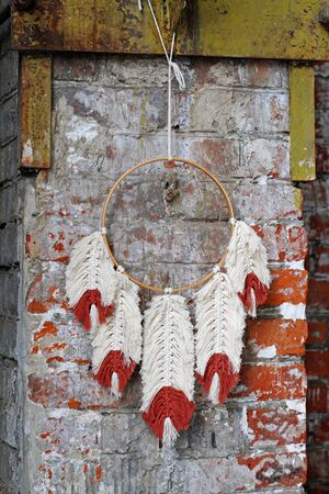 White-red macrame feathers  hang on round dreamcatcher against a brick wall.