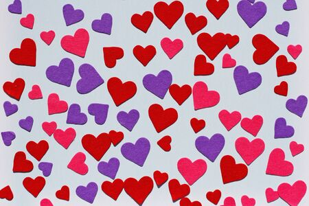 Red, pink and purple felt hearts on blue background