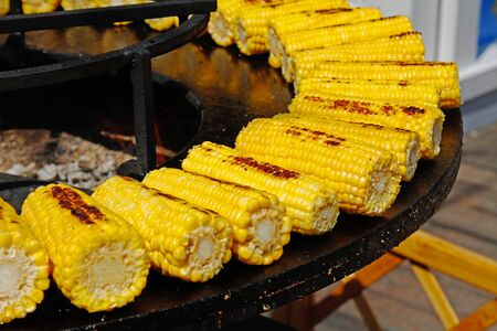 Delicious golden corns on large barbecue fire bowl