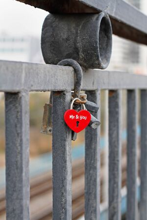 Red padlock in the form of heart and with the words Me&you hanging on fence