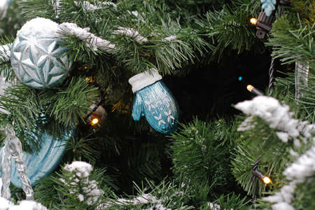 Christmas toy knitted mitten hanging on Christmas tree Foto de archivo