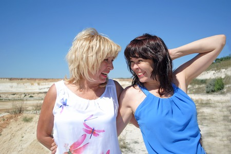 two generations: Two women of different ages standing and laughing. Warm family relationships. Blonde and brunette, mother and daughter, the succession of generations.
