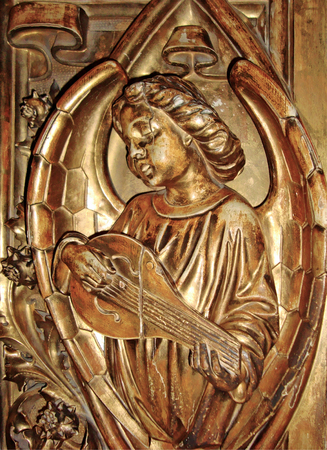 bas relief: An angel playing a musical instrument. The figure, bas relief of the angel with the lute is made of wood and covered with gold leaf. Stock Photo