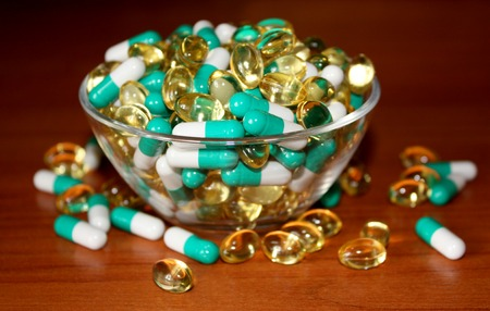 A scattering of tablets in a transparent bowl. Pills on a wooden background. Advertising a Healthy lifestyle, but also the possibility of addiction to the medication and excess dosage. Horizontal.