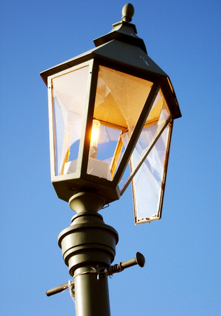Streetlight burning during the day as a symbol of waste, losses and vandalism. Broken hooligans street lamp.