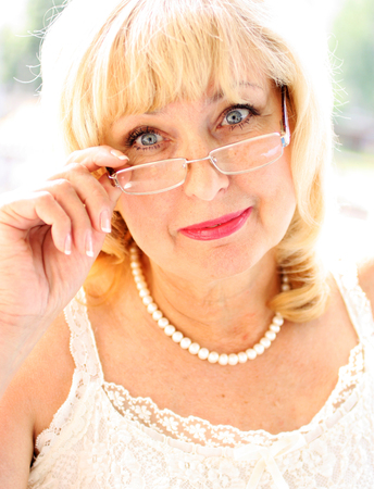 Portrait of smiling attractive senior lady in elegant garment. Living positively beautiful mature woman with glasses. Positive attitude towards life. Vertical. Standard-Bild