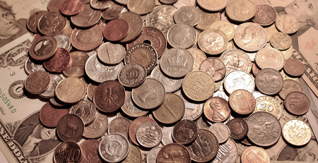 Background of coins lying on banknotes of United States. Currencies of different countries. Backdrop of scattering metal cash on dollars. Huge pile of coins on paper money. Horizontal location.