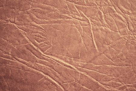 Colored skin texture, natural or faux leather background. Light brown leatherette, closeup.