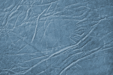 Colored skin texture, natural or faux leather background. Blue leatherette, closeup.