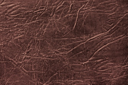 Colored skin texture, natural or faux leather background. Brown leatherette, closeup.
