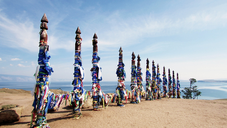 Vivid colored ribbons Hadak tied on posts of wish. Wooden ritual pillars. Sacred place of Buddhist shamans, Baikal, Russia. Mystical traditions of Asia.