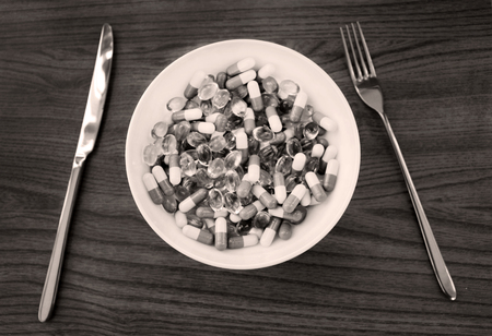 Pills and capsules in white deep plate with fork and knife. Advertising Healthy lifestyle, possibility of addiction to medication and excess dosage. Concept of good for health food, diet.
