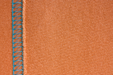 Empty orange knitted fabric with decorative elements. Knit texture with stitching.