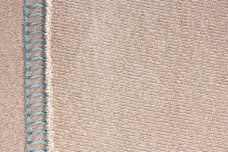 Empty beige knitted fabric with decorative elements. Knit texture with stitching.