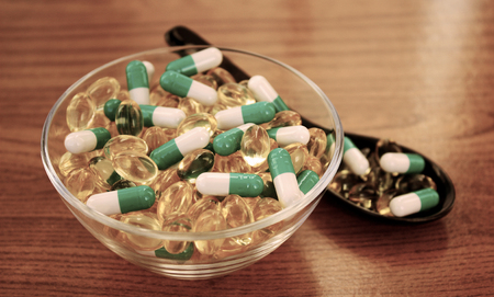 Scattering of different tablets. Pills in bowl on wooden