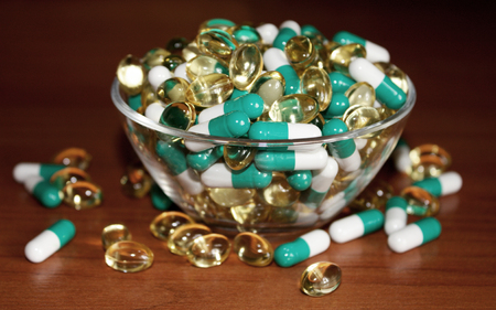 A scattering of tablets in a transparent bowl. Pills on a wooden