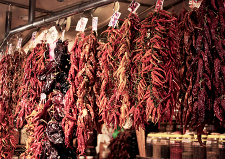 Bundles of red hot peppers hanging at a local farmers market, Spain.