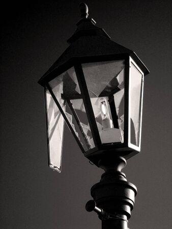 Broken lantern is lit against dark sky. 免版税图像