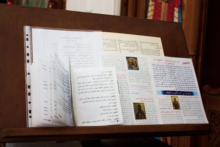 Various religious Scriptures lie on wooden stand for Bible in Church.