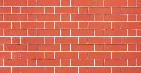 Orange brick wall. Light red background of masonry. Texture stained blocks of stonework. Plastered facade of building.