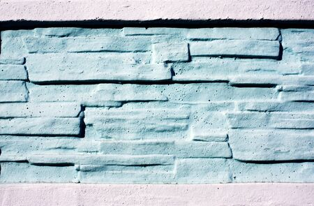 Texture stained blocks of stonework. Plastered facade of building of modern blocks tiles. Fence of facing stone. Brick wall in white and light blue colors.