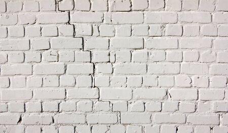 White brick wall. Light background of cracked masonry. Old texture stained blocks of stonework. 免版税图像