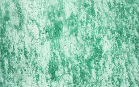 Shabby old fence covered faded green paint with light smudges on stucco. Vintage background for your design. Abstract grunge texture of peeling paint on worn wall.