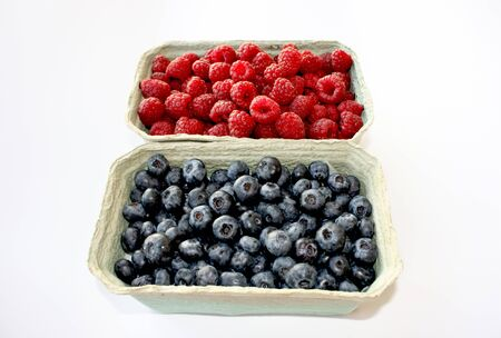 Background of sweet raspberry and blueberry in packing containers, cardboard boxes with berries. Red and blue fruit in package, closeup. Healthy, delicious dessert in packaging.