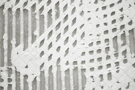 Background of old tile adhesive on wall being repaired. Abstract pattern of notched trowel. 免版税图像 - 138291243