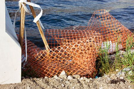 Plastic orange mesh and wooden fragments lying on coast of sea. Garbage polluted shore of river. Ecology, concept of environmental protection. 免版税图像 - 138637130