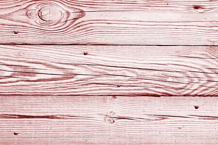 Background of light red wood boards. Wooden flooring, timbered floor, pale pink covering. Rustic backdrop of old panels with nails. Vintage wooden texture of fence. Natural pattern for wallpaper. 免版税图像