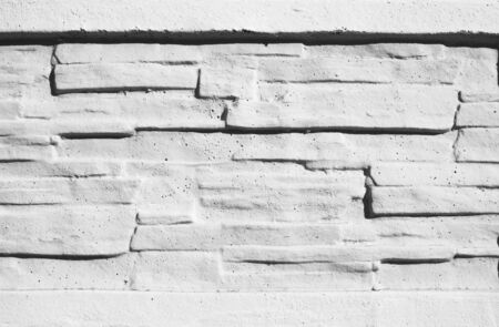 Texture stained blocks of stonework. Plastered facade of building of modern blocks tiles. Grey fence of facing stone. White brick wall.