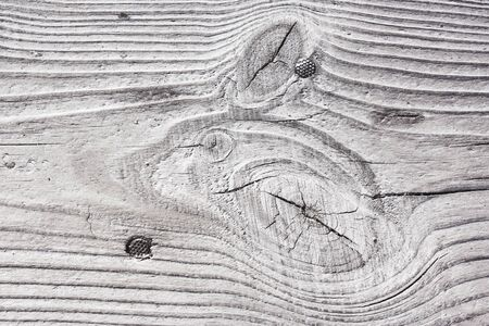 Background of natural wooden texture. Close-up wood board with naturally relief. Beautiful nature pattern of white old cracked timber with nails.