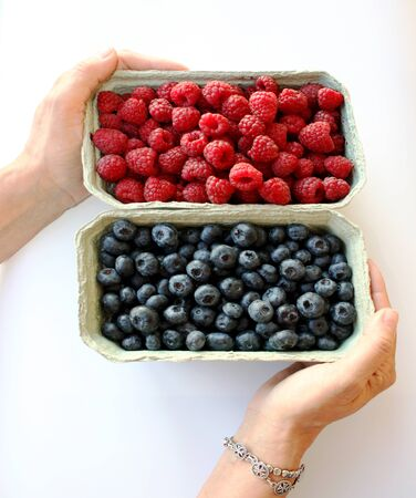 Photo of sweet raspberry and blueberry in packing containers. Womans hand holding boxes with berries. Red and blue fruit in package, closeup. Healthy, delicious dessert in packaging. Isolated. 免版税图像