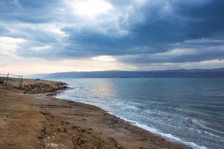 Deserted shore of Dead sea on the Jordanian side in off-season, view of Israel. Beach is closed during coronavirus infection, COVID-19. Abandoned fenced territory. 免版税图像 - 151938862