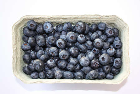 Sweet blueberry in packing containers, cardboard boxes with berries. Blue fruit in package, closeup. Healthy, delicious dessert in packaging.