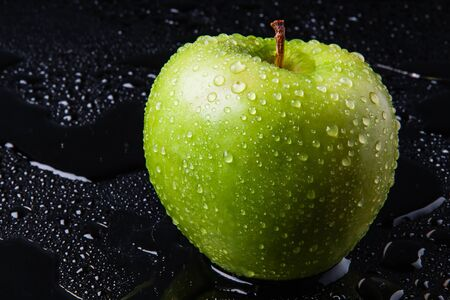 green Apple with yellow autumn leaves and a branch in the water Stock Photo