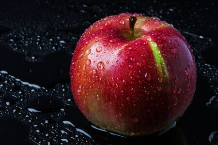 striped Apple with drops of rain, on the wet black glass