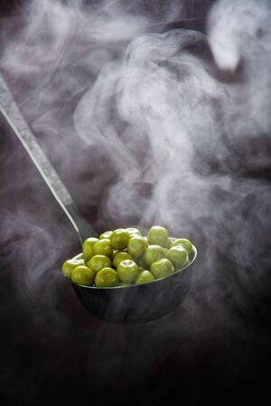 Freshly steamed green peas in an iron ladle