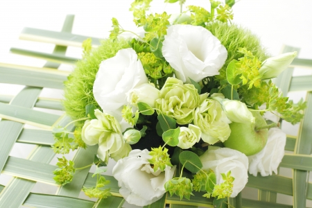 Bouquet from different white seasonal flower and green in basket photo