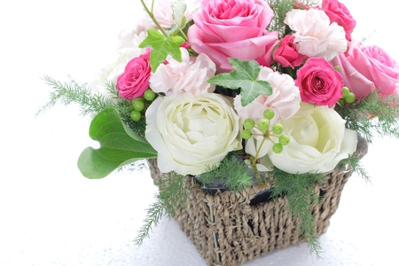 Bouquet from different pink seasonal flowers in basket isolated on white photo