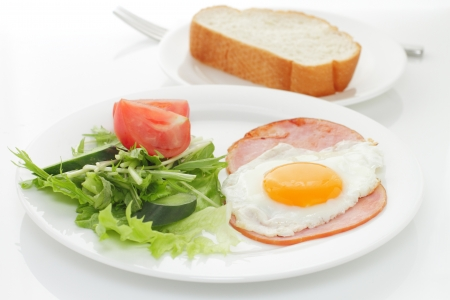 american breakfast with egg, ham, bread and vegetable photo