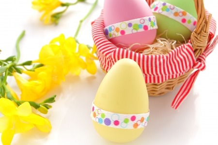 Colorful easter eggs with yellow freesia flowers photo